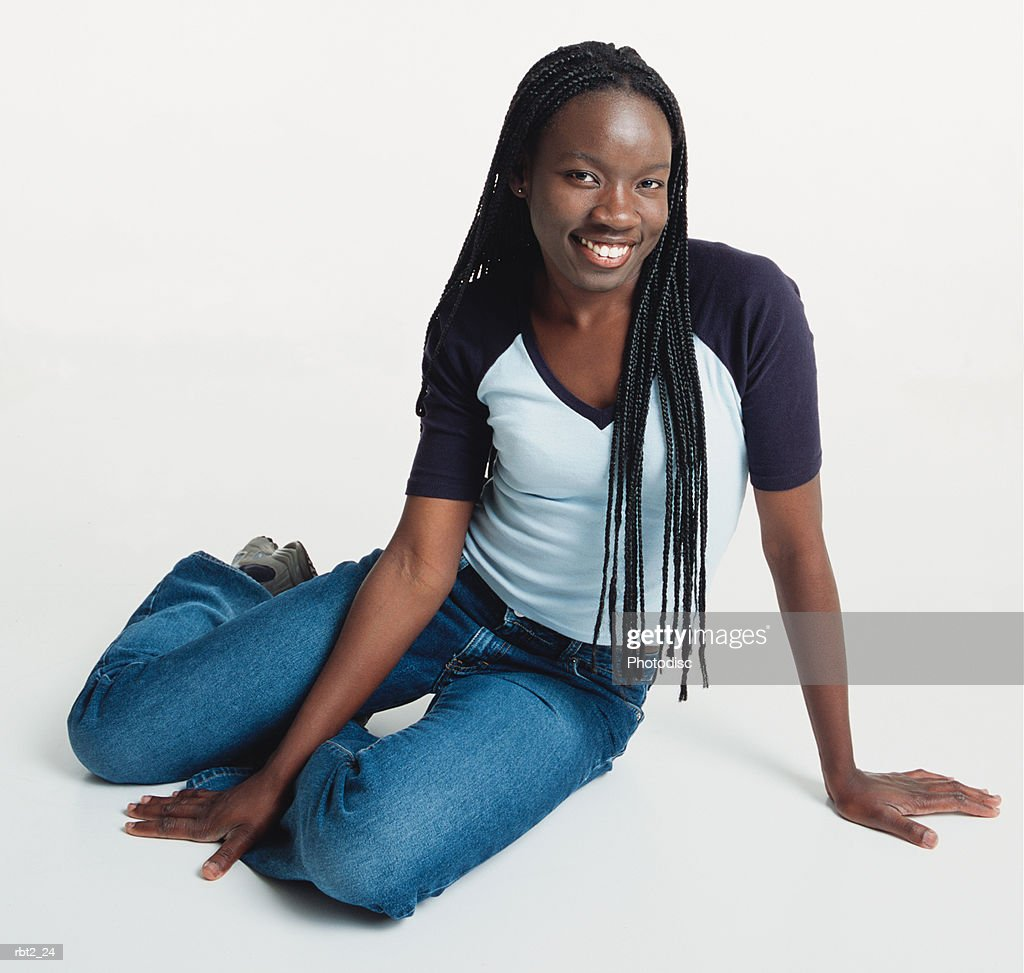 a beautiful young black woman with long cornrows sitting sideways on the floor wearing jeans and a teeshirt smiles at the camera : Foto de stock
