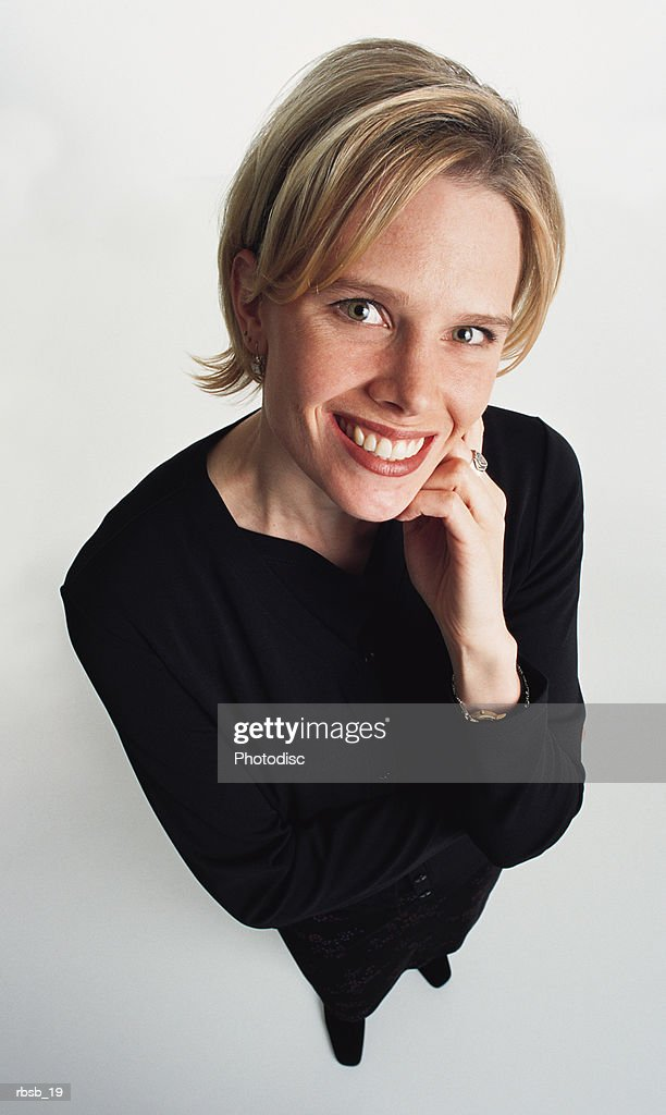 a beautiful young blond haired woman in a black suits stands smiling with her chin resting on her hand while looking up at the camera : Foto de stock
