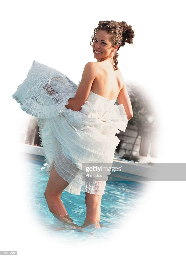 a beautiful young brunette hispanic or caucasian woman is wading in a pool as she gathers her lacey white strapless dress in her arms and smiles over her shoulder : Foto de stock