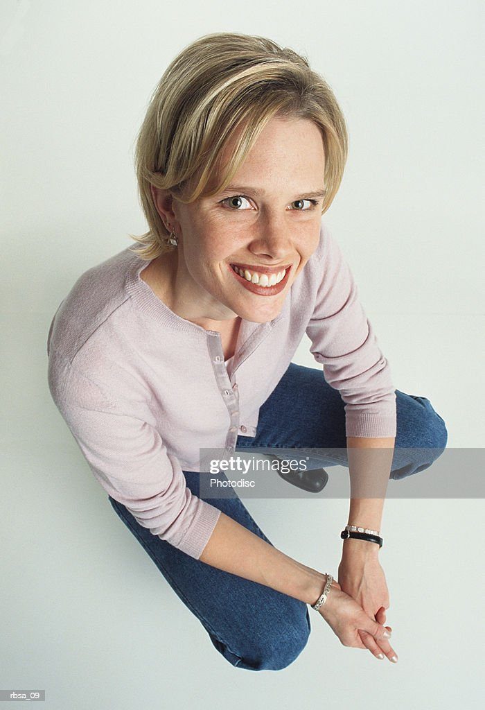 a beautiful young caucasian adult female wearing a cream colored cardigan and jeans kneels down while looking up at the camera smiling attractively : Foto de stock