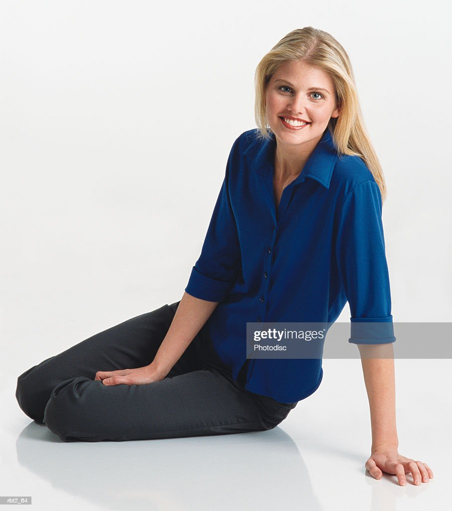 a beautiful young caucasian woman with long blond hair is wearing a blue blouse and sitting on the floor leaning toward the camera : Foto de stock