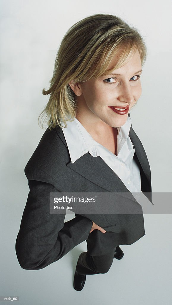 a beautiful young caucasian woman with shoulder length blond hair in a dark grey business suit looking up into the camera with her hands on her hips : Foto de stock
