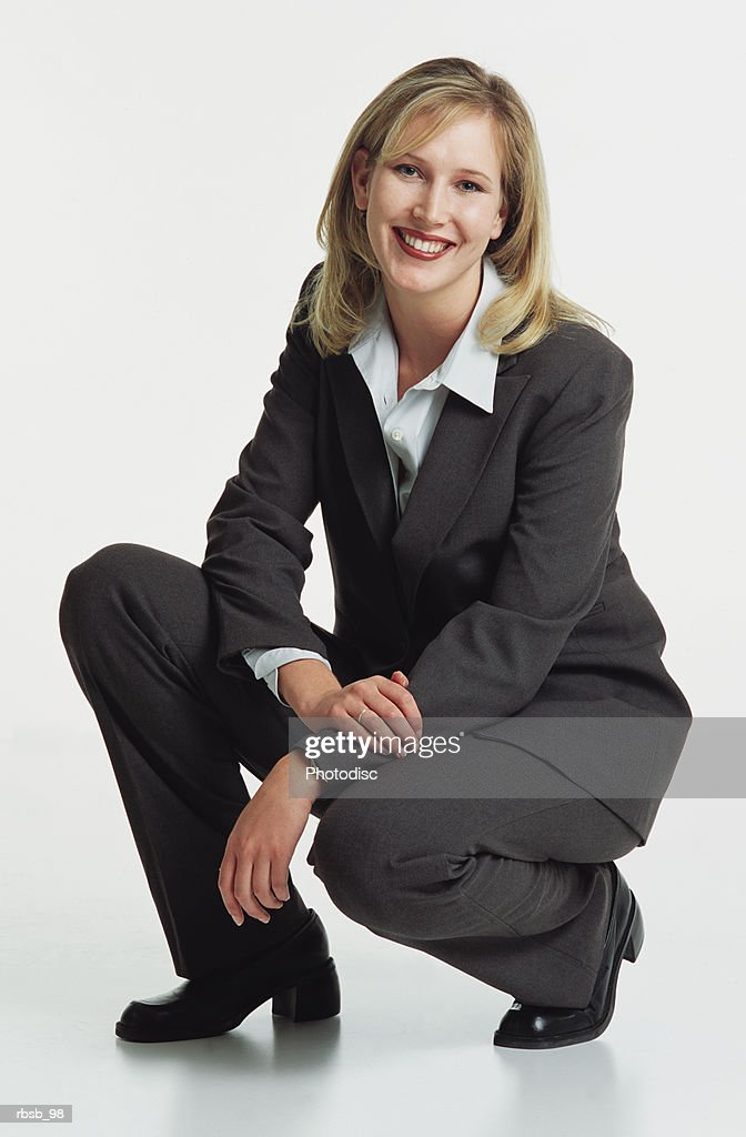 a beautiful young caucasian woman with shoulder length blond hair in a dark grey business suit in a crouched position looking into the camera : Foto de stock