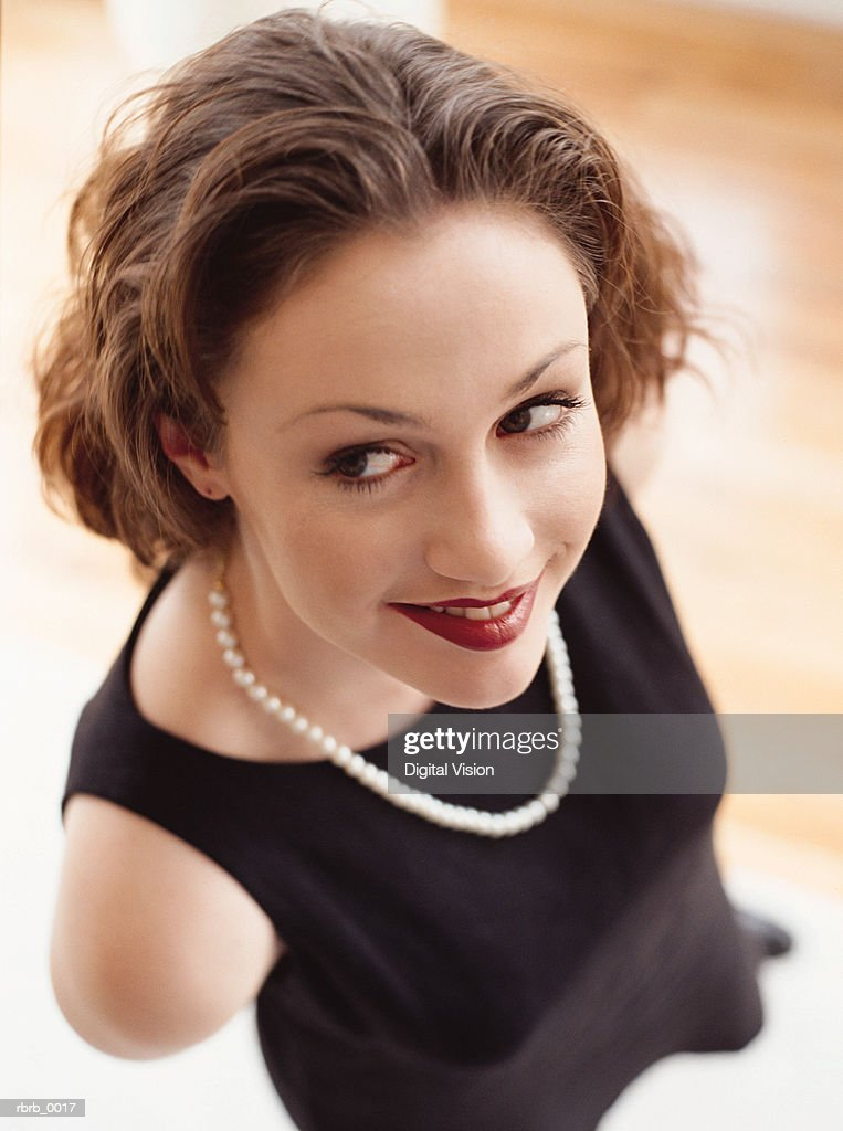 a beautiful young girl seen from above is dressed up in a black dress and a string of pearls as she smiles slyly : Stockfoto