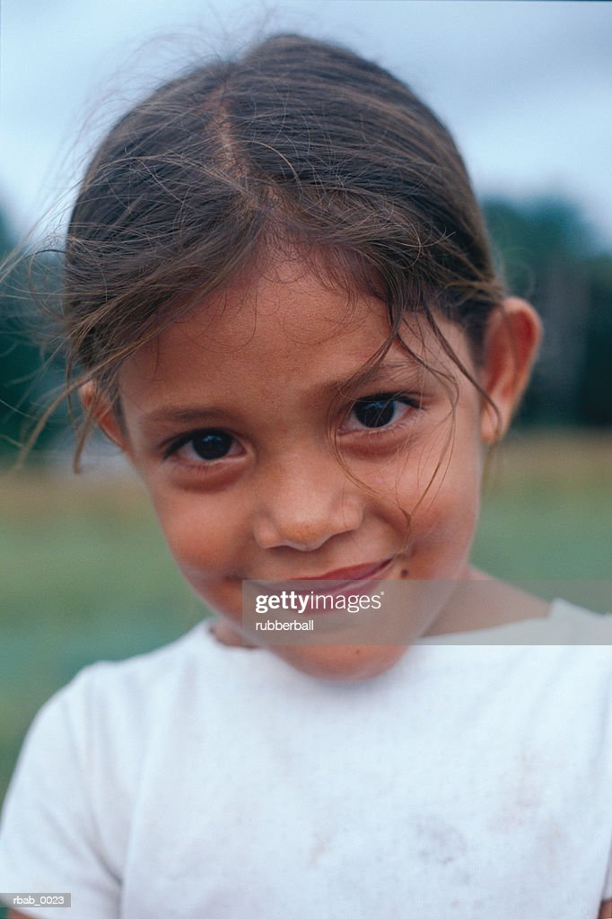a beautiful young latin girl is smiling shyly at the camera in costa rica : Stockfoto