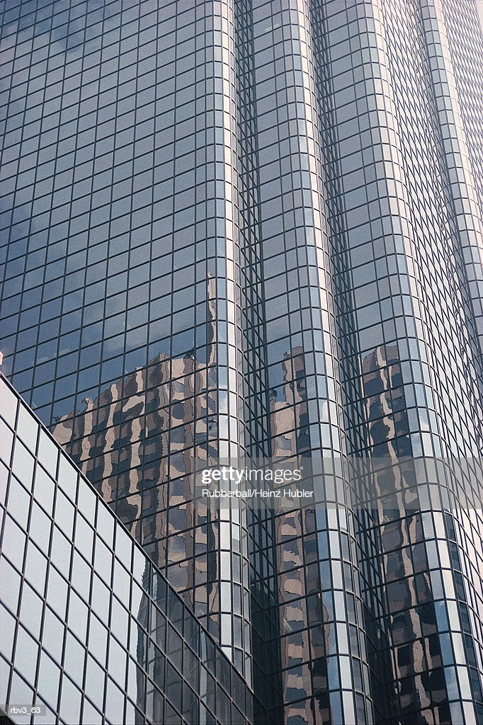 a beige skyscraper and the blue sky with white clouds can be seen in the reflective windows of a silver building : Foto de stock