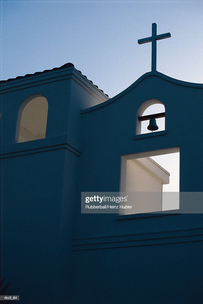 a bell hangs from a white stucco mission home under a blue sky : Foto de stock