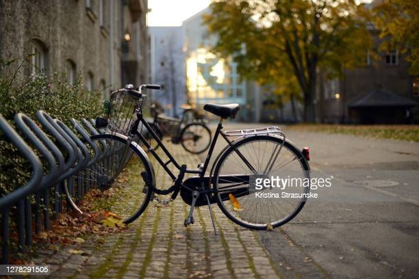 a bicycle parked by a buildings, surruonded by trees in autumn colors, beautiful sunset light coming through one of the buildings - kristina strasunske stock pictures, royalty-free photos & images