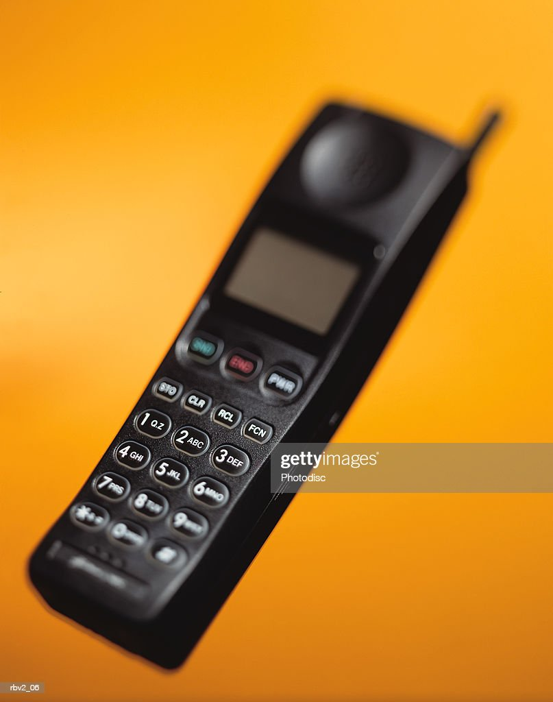 a black cellular phone suspended in air in front of a yellow background : Foto de stock