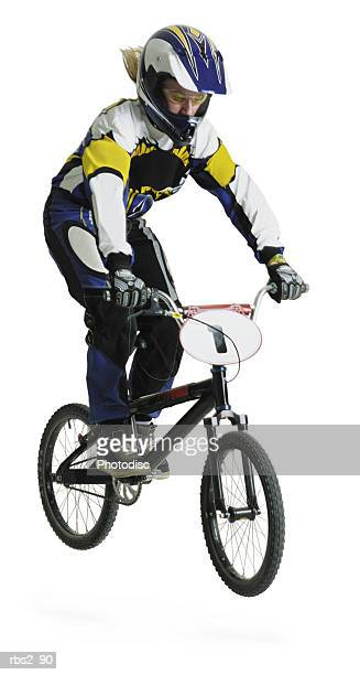 a blond caucasian teenage girl wearing a bike racing suit and helmet is airborne on her dirtbike - bmx cycling stock pictures, royalty-free photos & images