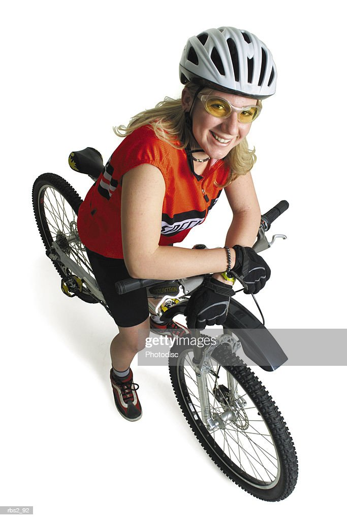a blond caucasian teenage girl wearing a red racing vest and a white helmet has on orange glasses as she sits on her bike and looks up at the camera : Foto de stock