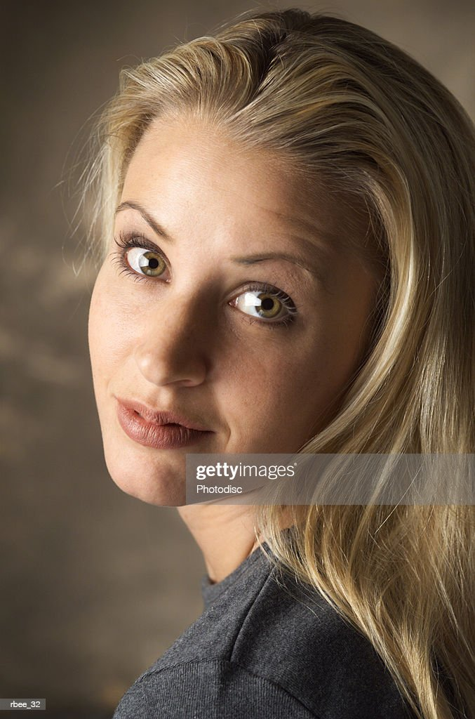 a blond caucasian woman in a gray t-shirt is looking over her shoulder at the camera as she grins : Stockfoto
