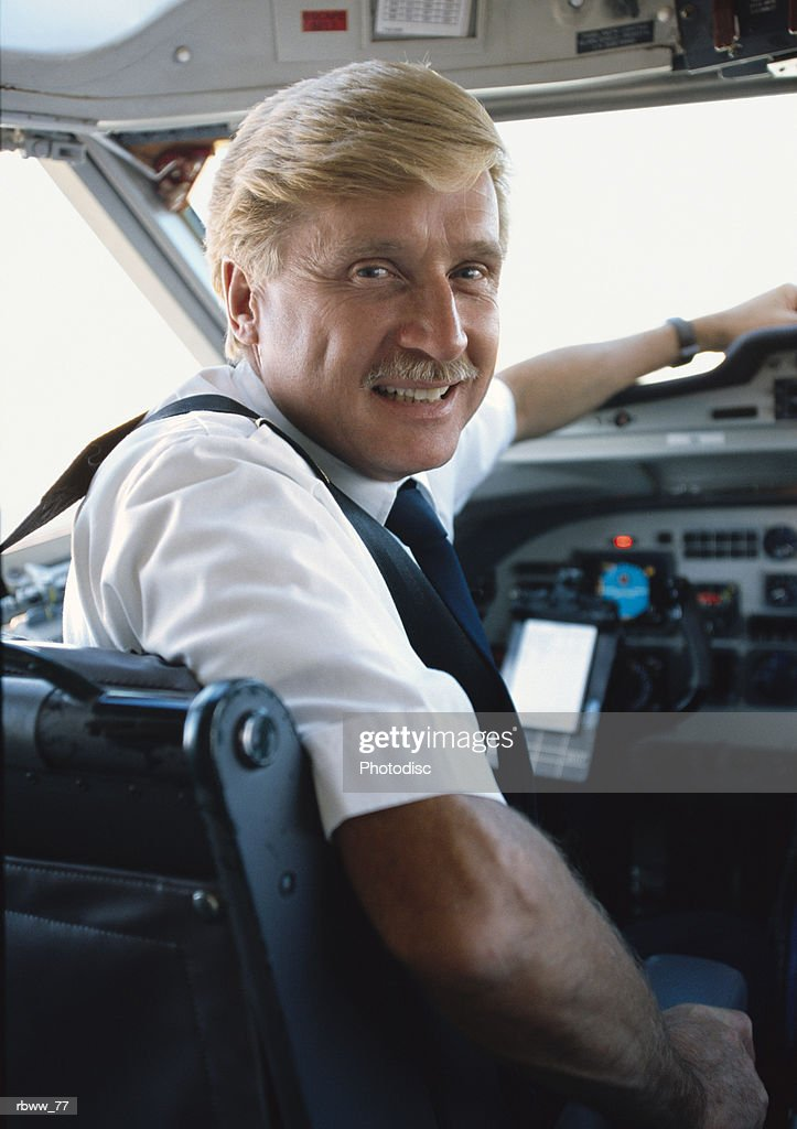 a blond cuacasian male airplane pilot smiles while sitting in the cockpit : Foto de stock
