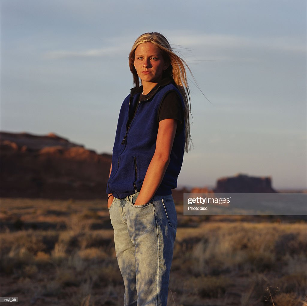 a blond haired young woman in blue jeans and a blue fleece jacket standing in southern utah desert : Foto de stock