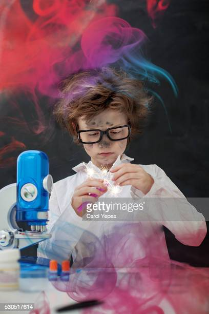 a blonde boy making some scientific experiments at class.