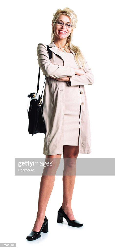 a blonde caucasian business woman stands with her arms folded while holding a black bag : Foto de stock