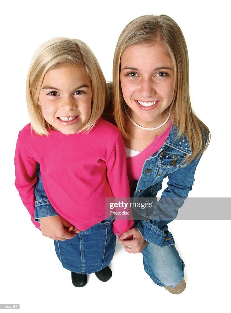 a blonde caucasian female teenager in a jean jacket crouches down and hugs her little sister : Foto de stock