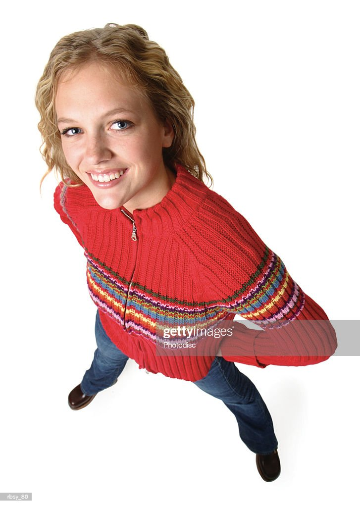 a blonde caucasian female teenager in jeans and a red sweater puts her hands on her hips and smiles up into the camera : Foto de stock