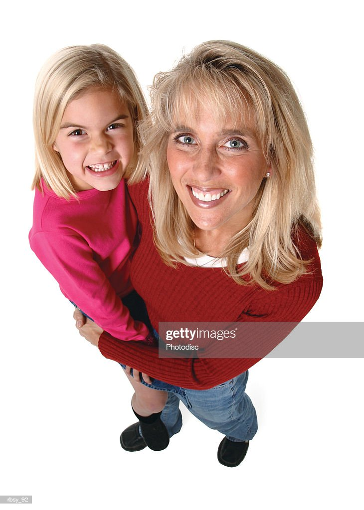 a blonde caucasian mother in a red sweater holds up her young daughter as they both smile up at the camera : Foto de stock