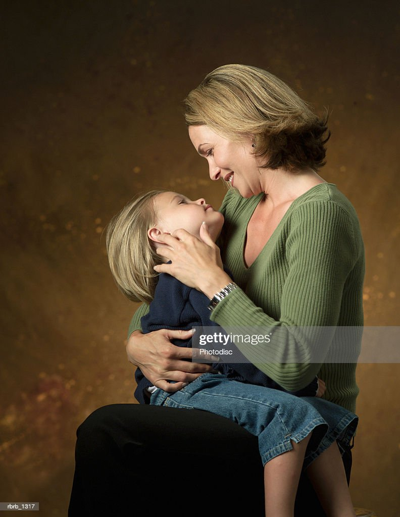 a blonde caucasian mother looks lovingly at her young daughter as she sits on her lap : Stockfoto