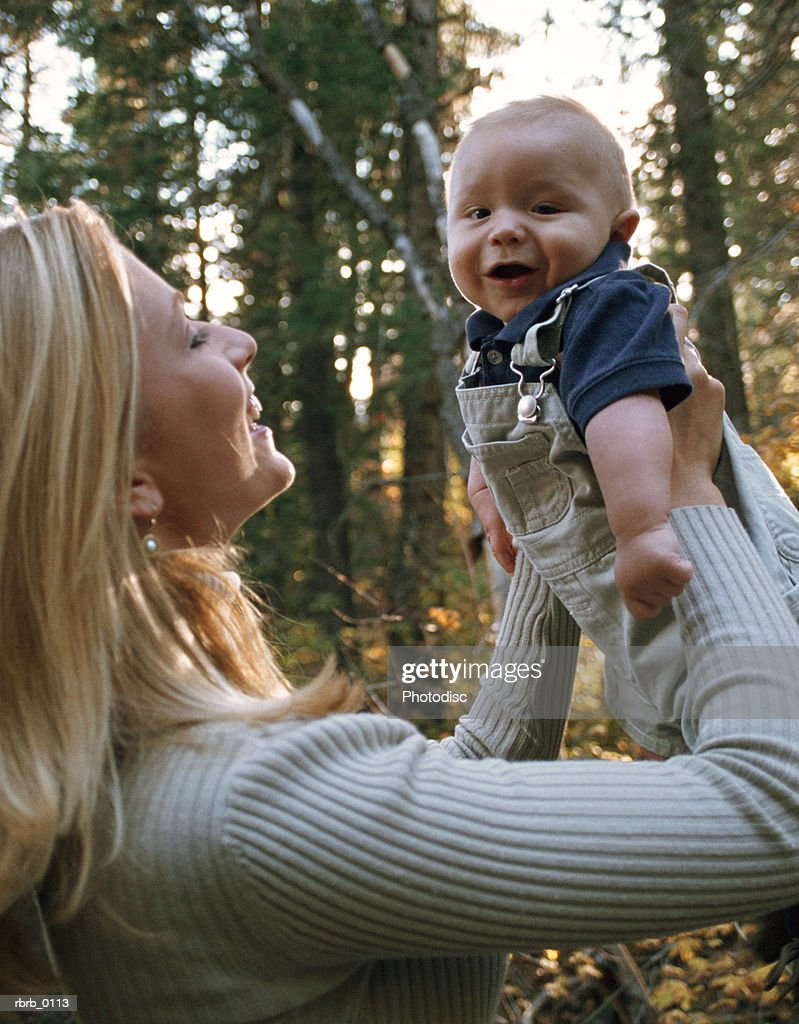 a blonde caucasian mother lovingly holds up her young baby and smiles : Stockfoto