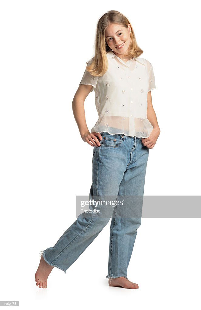 a blonde caucasian teenage girl wearing blue denim jeans and white shirt places her hands on her hips as she smiles at the camera : Foto de stock
