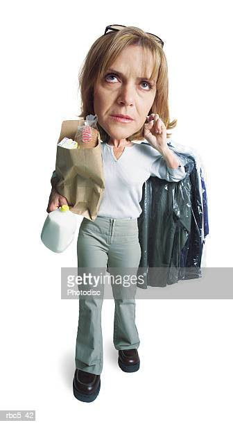 a blonde caucasian woman is walking and holding groceries and dry cleaning while looking annoyed and exhausted