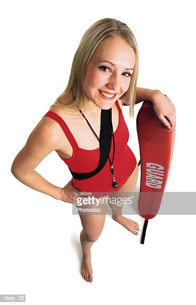 a blonde female lifeguard in a red swimsuit stands with her rescue tube as she smiles and looks up at the camera - vertical red tube fotografías e imágenes de stock
