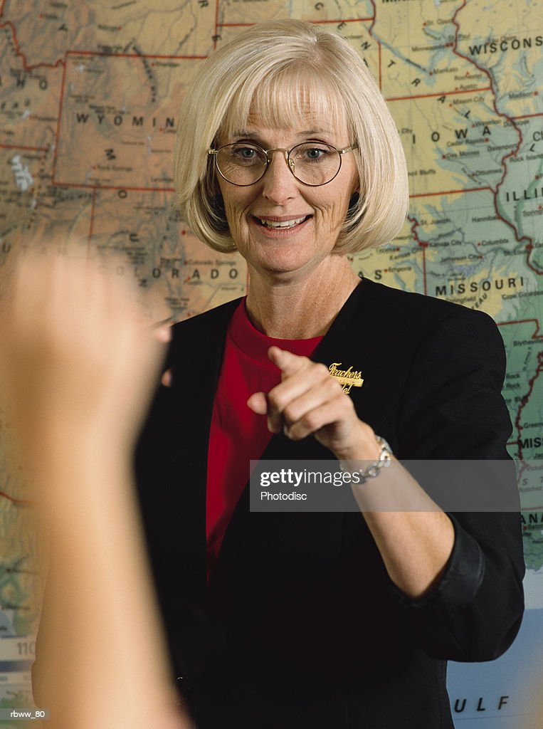 a blonde female school teacher points to a student with a raised hand during class : Foto de stock