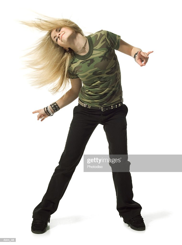 a blonde female teen in black pants and a camouflage shirt dances playfully : Foto de stock