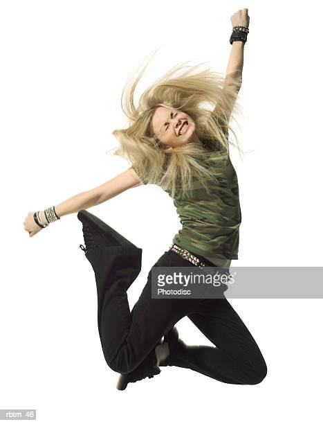 a blonde female teen in black pants and a camouflage shirt jumps up wildly