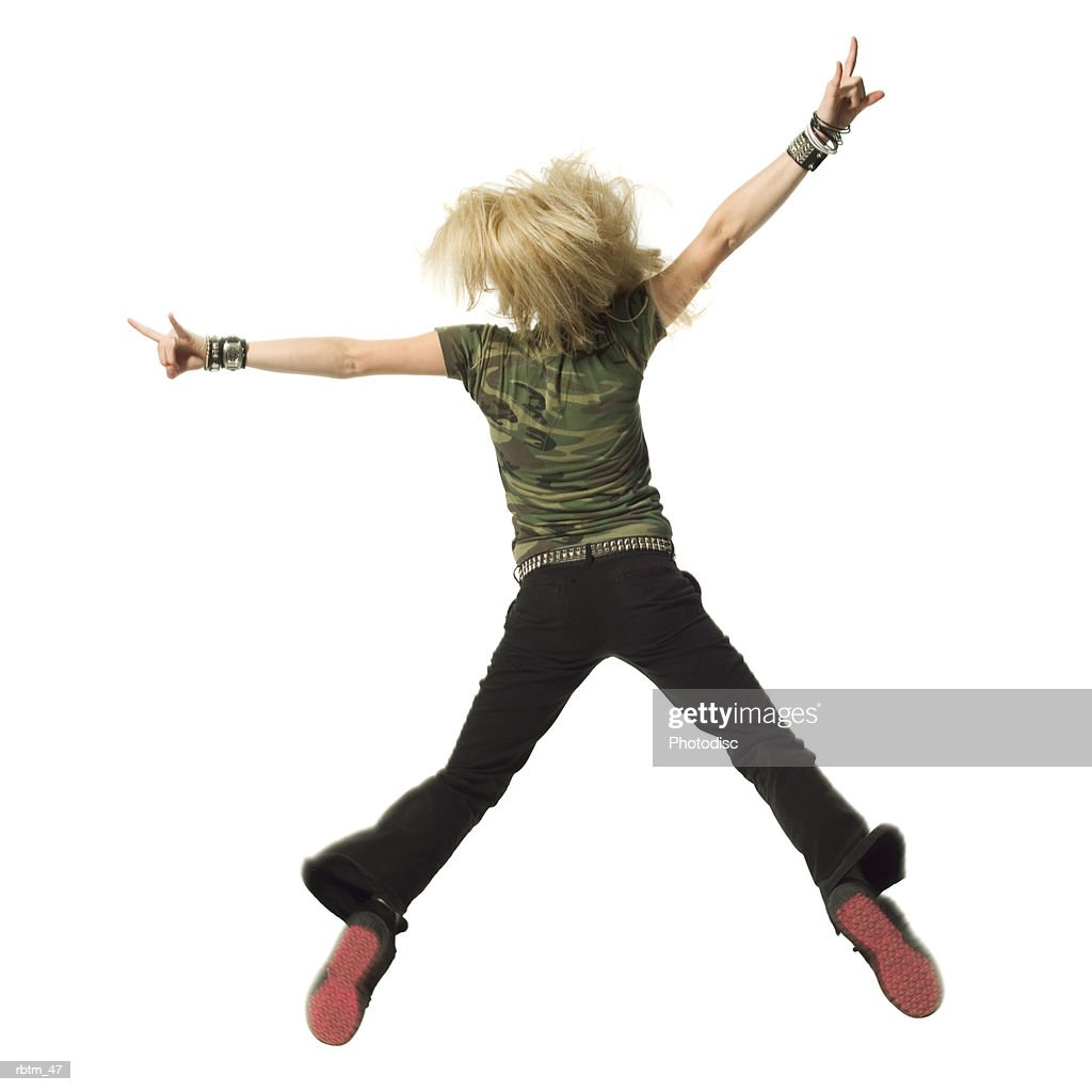 a blonde female teen in black pants and a camouflage shirt jumps up and throws her arms out : Foto de stock