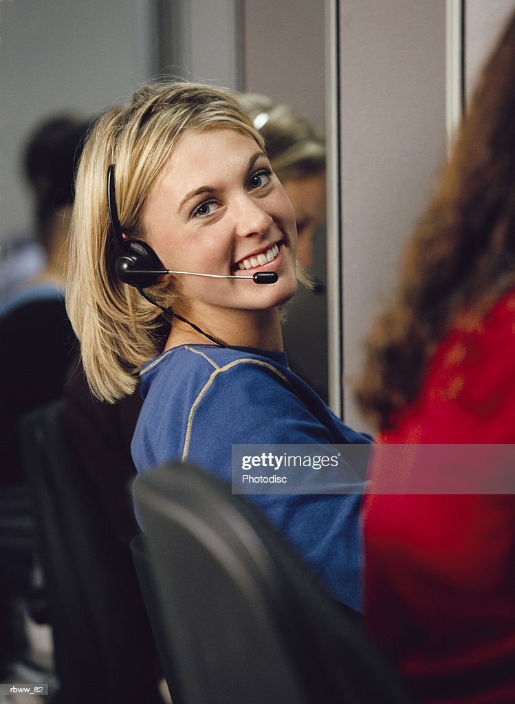 a blonde female telemarketer wearing a headset sits at her cubicle and smiles : Foto de stock