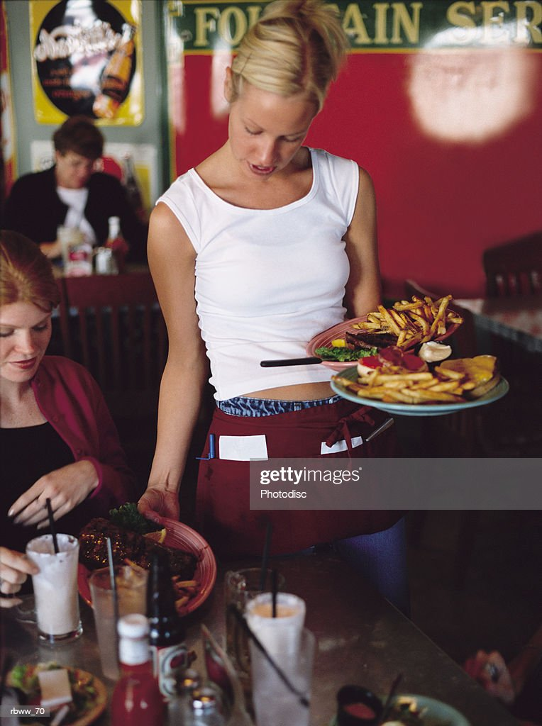 a blonde waitress delivers a meal to her customers : Foto de stock