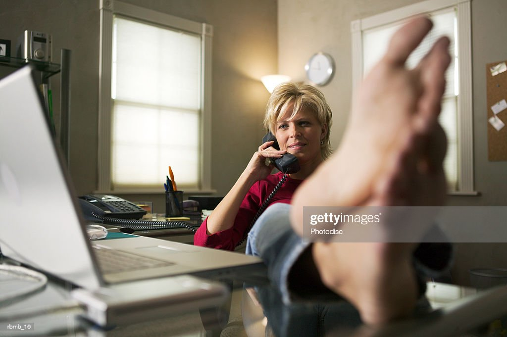 a blonde woman leans back in her chair while on the phone and puts her bare feet on the desk : Stockfoto