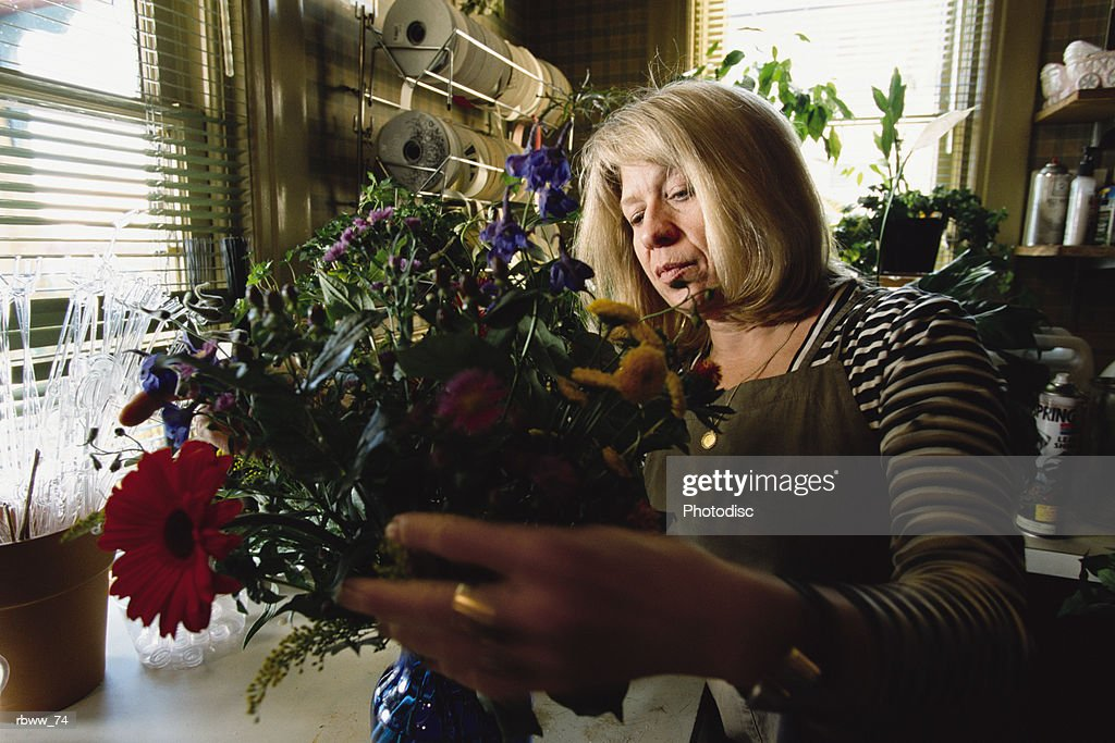 a blonde woman works as a florist at a flower shop : Foto de stock