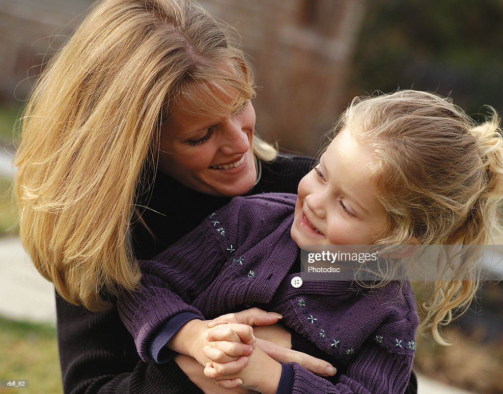 a blone happy mother hold daughter and makes her laugh : Stockfoto
