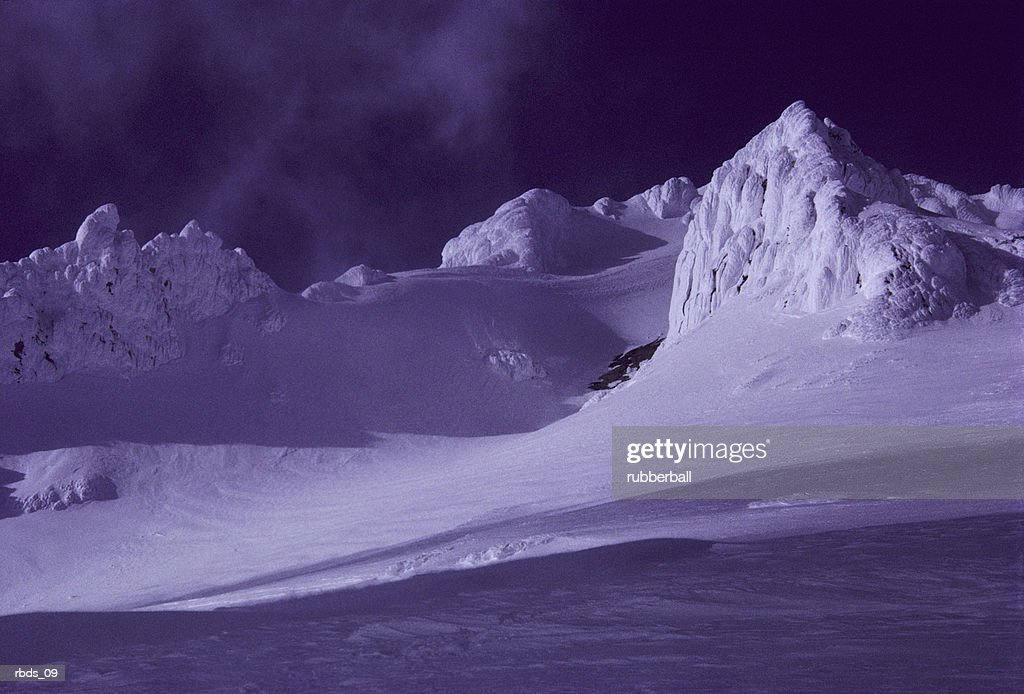 a blue snow covered mountain range at night : Stockfoto