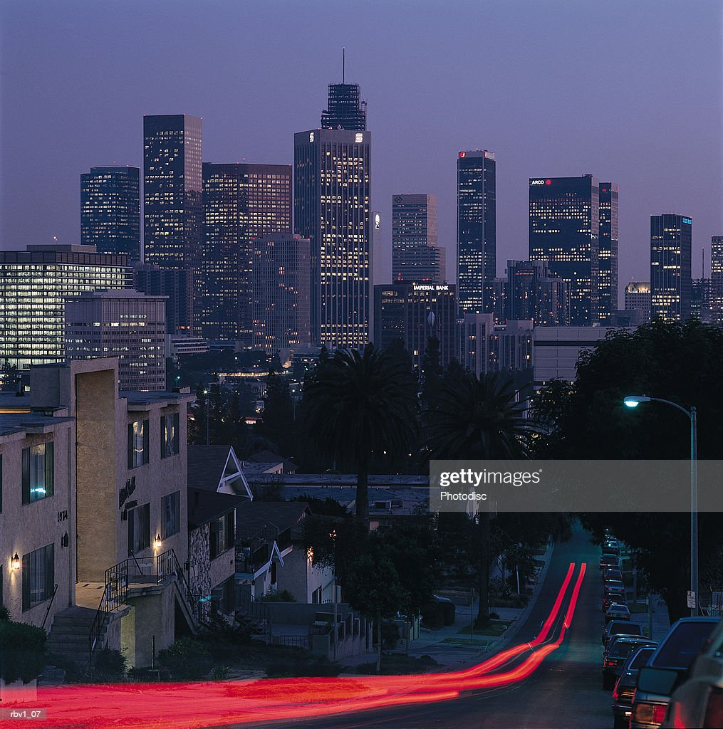 a blur of brake lights going down a road on a hill leading to Los Angeles with cars and buildings lining the road : Foto de stock