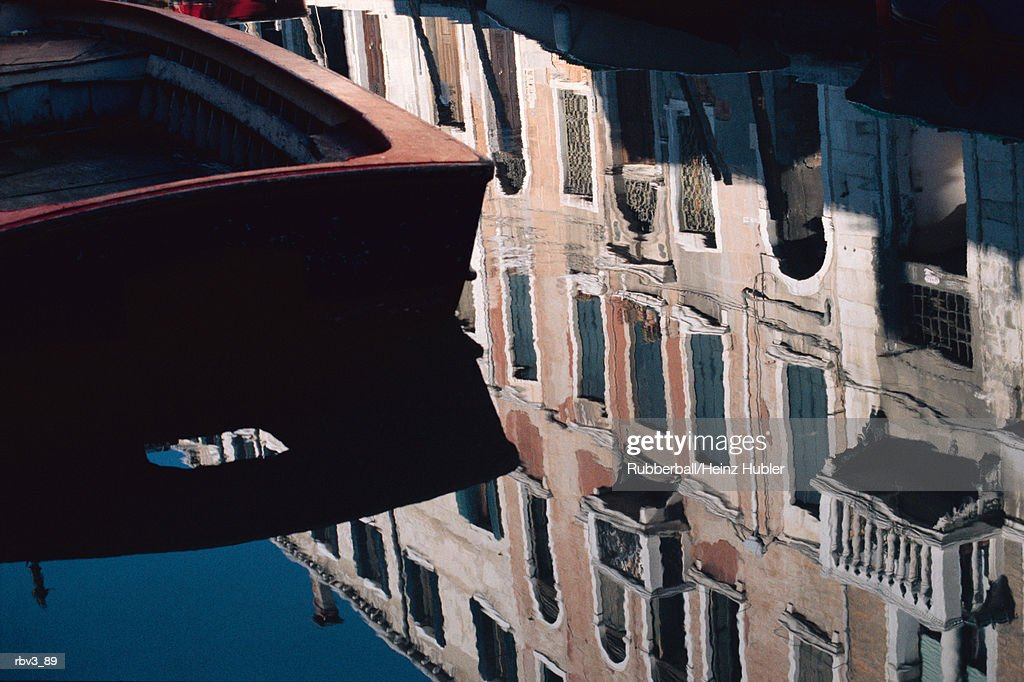 a boat floats on a canal that reflects the blue sky and buildings with windows : Foto de stock