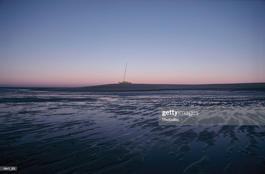 a boat rides a wave in the distance of a barren shore as the sun sets making the sky blue and pink : Foto de stock