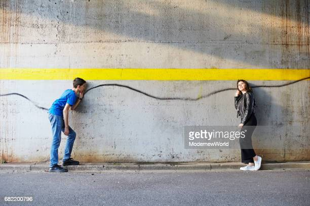 a boy and a girl pretending to connect with the sprayed line