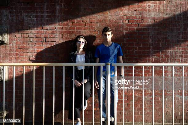 a boy and a girl standing in front of the red brick wall