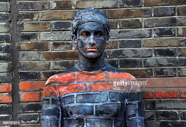 "A boy disguised as a wall is seen near New World street on April 10, 2015 in Shanghai, China. A boy ""hides"" himself by being painted the same color..."
