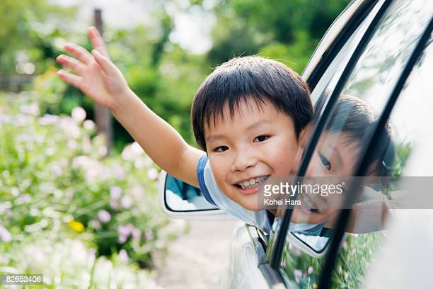 a boy in a car waving his hand