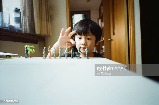 a boy is playing his toy soldiers. - army soldier toy stock pictures, royalty-free photos & images