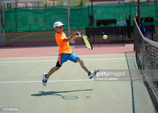a boy is playing tennis on the hardcourt with forehand - hardcourt stock pictures, royalty-free photos & images