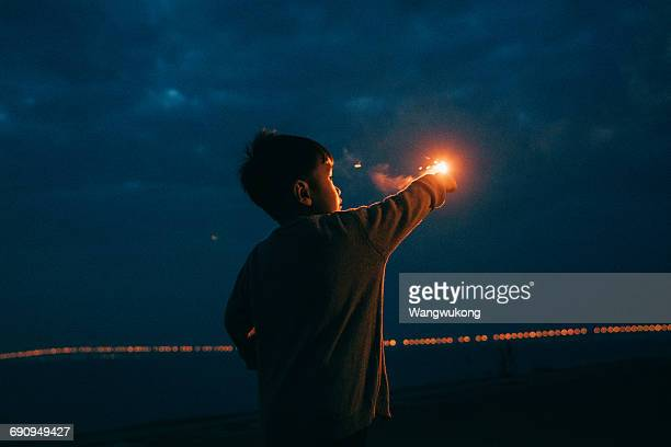 a boy playing with fireworks - long sleeved stock pictures, royalty-free photos & images