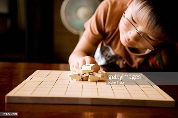 a boy playing with shogi pieces