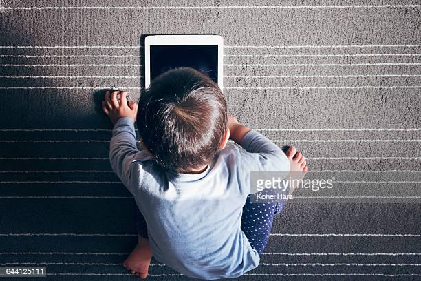 a boy using a tablet pc on carpet